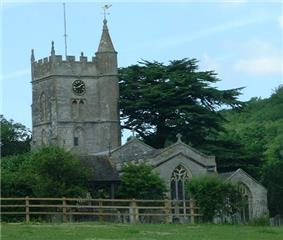 Gray stone building with arched windows. Square tower topped with spirelet, flagpole and weather vane. Foreground has small trees and bushes and a wooden rail fence.