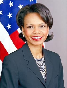Condoleezza Rice smiling with thickly applied red lipstick wearing a dark blue jacket over a patterned blouse. The United States flag is in the background.