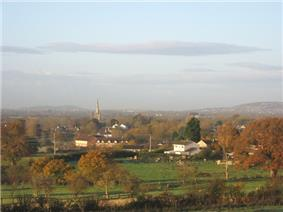 Roofs of houses showing amongst tree with prominent church tower. In the foreground are green fields with hills behind.