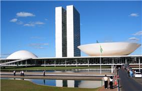 The view shows a 20th-century building with two identical towers very close to each other rising from a low building which has a dome at one end, and an inverted dome, like a saucer, at the other.