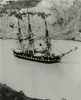 Photograph of a ship being towed through a canal