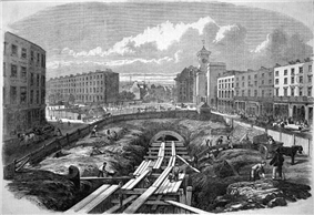 Etching, showing a large, deep cutting taking up width of the road. The excavation is filled with scaffolding and the partially completed and covered-over tunnel is beyond