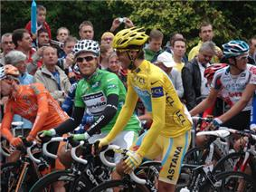 A man in yellow clothes. In the background people are watching.