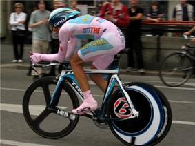 A cyclist wearing a pink skinsuit while riding a bike.