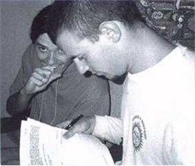 Black and white photo showing two men. Man at left is leaning forward, biting the knuckle of his right fore-finger. He is partly obscured by the next man who is shown in left profile, he is holding a typed document and is looking down at it. He has a pen in his right hand, his left is out of shot.