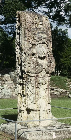 Intricately carved free standing stone shaft sculpted in the three-dimensional form of a richly dressed human figure, standing in an open grassy area.