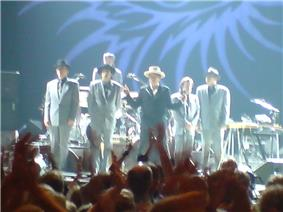 heads of people cheering in front of Dylan acknowledging five band members for the most part in grey suits wearing black hats
