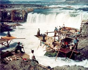 Men sit on scattered wooden platforms surrounding a waterfall that is about 25 feet (7 meters) high and 250 feet (70 meters) wide. The men hold long poles attached to nets that are in the water.