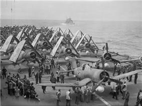 Black and white photo of a large number of single-engined monoplane aircraft on the deck of an aircraft carrier at sea. Another ship is visible in the background.