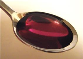 Close-up photo of a metal spoon filled with a viscous, clear purple fluid