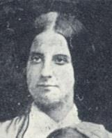Black and white photograph showing the head and shoulders of a woman with dark hair wearing a dress with a large, white collar