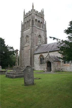 Stone building with arched porchway. Prominent square tower to the left hand end of building. In the foreground gravestones and crosses on grass.