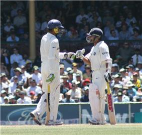 Two men wearing white uniforms shirts and trousers, blue helmets, gloves, pads and holding cricket bats meet one another on a cricket pitch to touch gloves. A crowd can be seen in the distance.