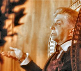 In this sepia-toned photograph, a straight-faced Quentin Crisp gestures from an ornate, high-backed chair. A large, red handkerchief flops from his jacket pocket.