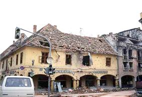 Two shattered arcaded buildings, one old and painted yellow, the other more modern and made of brick and concrete, with destroyed roofs and many bullet holes. In front is a damaged traffic signal and a car.