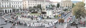Small photo of people in folk costume in a city square