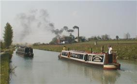 A straight section of canal going into the distance, with two passing  narrow boats in the foreground, with a large brick building and tall chimney in the middle-distance on the right bank of the canal. Smoke is billowing from the chimney, blowing across the canal to the left.