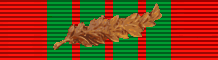 alt:Red ribbon with vertical green stripes in the center and a palm leaf in the middle