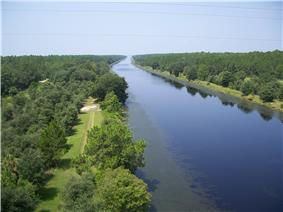 View down on a canal approximately 100 feet across disappearing into the horizon, bordered by trees
