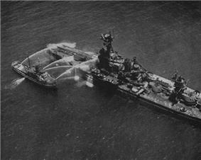 A large, damaged, stripped warship being hosed down by a smaller boat