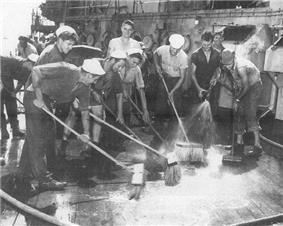 Sailors scrubbing down a ship deck.