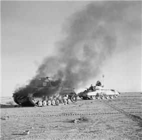 Crusader tank passing burning Panzer IV tank during Operation