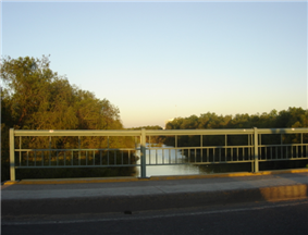 A medium-sized river seen from a bridge with a metal railing.
