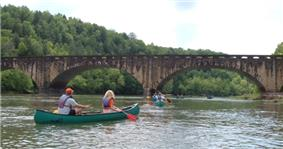 Several canoes pass under a bridge over a wide river in a forest.