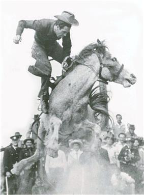A man dressed in cowboy-style is in mid-air above the back of a horse bucking in a cloud of dust