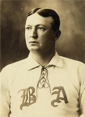 A black-and-white photograph of a man from the chest up looking to his right, wearing a baseball uniform with the letters