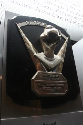 A metal hand grips a metal baseball on a black plaque; the inscription reads