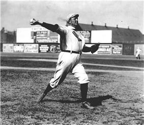 A man in a white baseball uniform and cap throws a baseball with his right hand. The shirt of his uniform has a sock-shaped icon, which reads