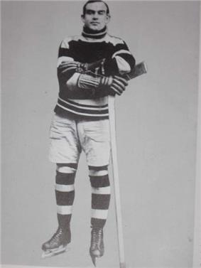 a black and white photo of a young hockey player standing on his skates with his arms folded leaning slightly on an upside down hockey stick