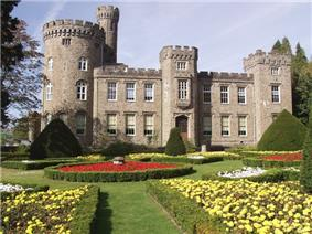 Victorian castellated mansion with a keep to the left and formal gardens in the foreground