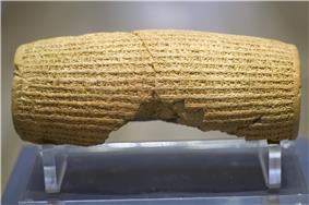 Rear view of a barrel-shaped clay cylinder resting on a stand. The cylinder is covered with lines of cuneiform text