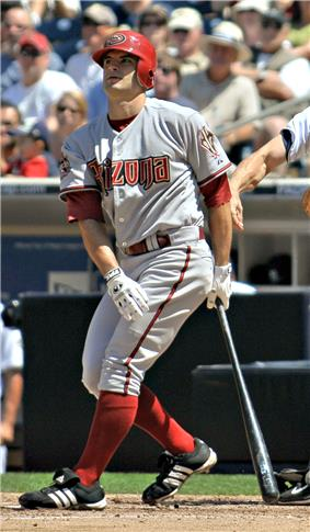 A man in red socks and a gray baseball uniform with