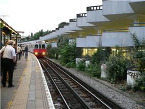 A group of people standing on a railway platform with a railway track to the right and a white-and-red train running on it with its headlights on