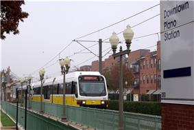 A white and yellow train arriving at a station with several lamp posts in the foreground, transit oriented development at the rear and station signage at the far right.