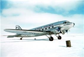 Right side view of a silver Douglas DC-3 aircraft parked on snow-covered ground.