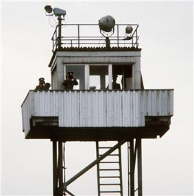 On top of a tubular steel support structure with a ladder there is a small cabin with windows to all sides, surrounded by a balcony on which stand two men in uniform, looking at the observer through binoculars; a third man is inside the cabin. There are searchlights on the tower's flat roof, and a railing around the roof's outer edge.