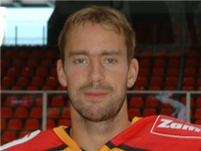 An ice hockey players face and shoulders. He has short brown hair and is not wearing a helmet.