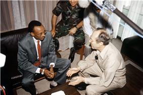 Overhead view of Kagame and Perry seated on leather seats with a large microphone visible and another army member in the background