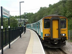 Four carriage train, on single curved track, at station. Steep wooded bank on one side of the track. Platform to the other. Station sign, in Welsh above English, in the foreground. Modern bridge over the track in the background.