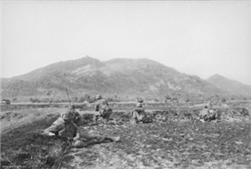 Soldiers wearing flak jackets and helmets are prone on an open field at the base of a large vegetated hill.