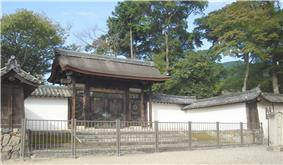 A small wooden roofed gate with chrysanthemum motifs and Chinese style gables on the side.