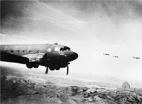Four twin-propeller aircraft fly over a mountain range