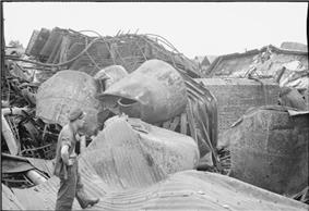 A man wearing military uniform looking towards a pile of damaged metal and concrete objects