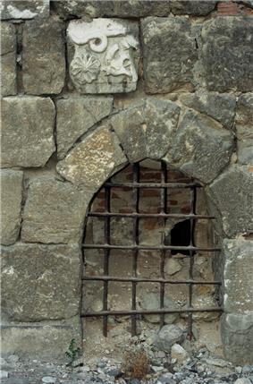A small gate with iron bars set in a wall built of uneven stones, one of which is decorated