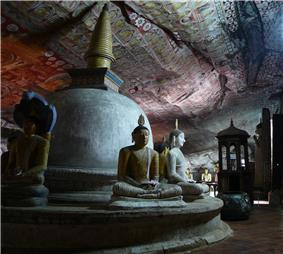 Stupa and statues of bodhisattvas inside a cave.