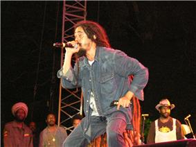 A man holding a microphone on a stage and wearing a blue denim jacket and jeans. Onlookers and a few microphone stand can be seen in the background.